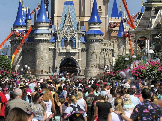 In this March 12, 2020, photo, a crowd is shown along Main Street USA in front of Cinderella Castle in the Magic Kingdom at Walt Disney World in Lake Buena Vista, Fla.