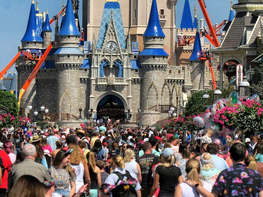 "FILE - In this March 12, 2020, file photo, a crowd is shown along Main Street USA in front of Cinderella Castle in the Magic Kingdom at Walt Disney World in Lake Buena Vista, Fla. As Walt Disney World prepares to allow some third-party shops and restaurants to open at its entertainment complex later this week, it's posting a warning. While enhanced safety measures are being taken at Disney Springs, ""an inherent risk of exposure to COVID-19 exists in any public place where people are present,"" the company said Monday, May 18, 2020, on a website for the entertainment complex.(Joe Burbank/Orlando Sentinel via AP, FIle)"