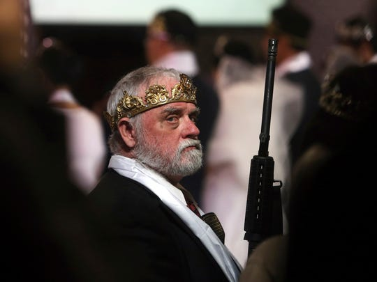 A man wears a crown and holds an unloaded weapon at
