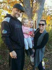 Rob Vite poses with his wife, Jade, and daughters,