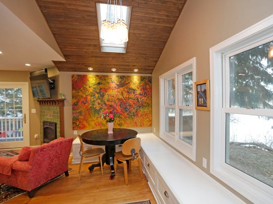 A small dining area sits near a built-in seating and storage bench. Karen Dredge received the large oil abstract painting on the wall from her mother; it was obtained from a California State University-Long Beach student art show in the 1960's.