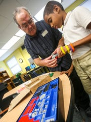Steve McCullough, gifted teacher, helps Darren Darnell,
