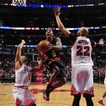 Atlanta Hawks guard Jeff Teague (0) goes to the basket on Chicago Bulls guard Derrick Rose (1) and forward Taj Gibson (22) during the second half of an NBA basketball game in Chicago, Monday, March 28, 2016. The Hawks won 102-100. (AP Photo/David Banks)