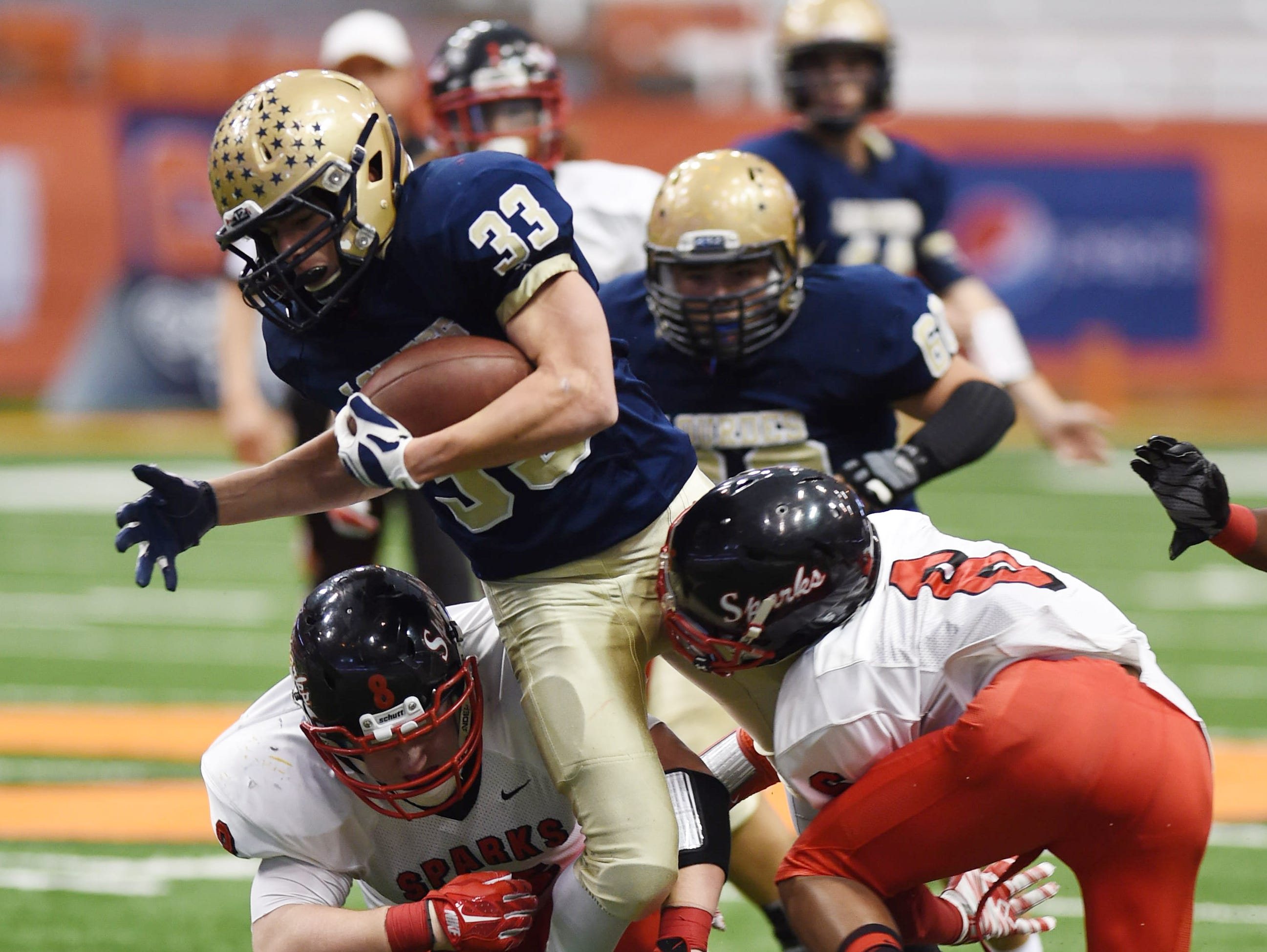 Lourdes' Christopher Salotto gets tackled by South Park's (from left) Nick Schaefer and Mike Mcdonald during the New York State Championship final in Syracuse on Friday.