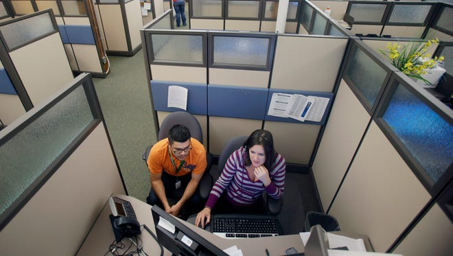 MNsure contact center representatives specialist Carlos Villanueva, left, and guide Emily Joyce work in one many cubicles at the center in St. Paul, Minn. in preparation for Tuesday, when the state's new online portal for delivering changes tied to the federal health care law opens for enrollment.