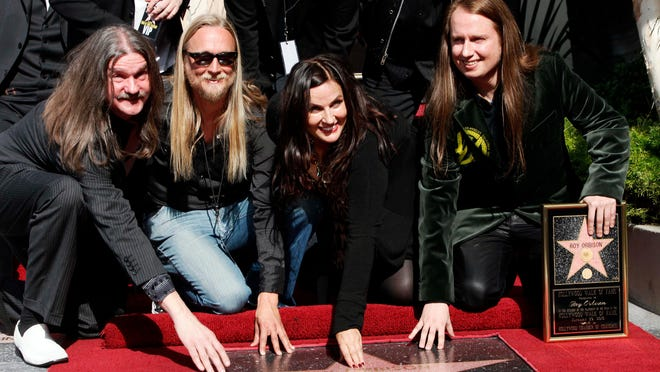 """FILE - In this Jan. 29, 2010 file photo, rock and roll legend Roy Orbison is honored with a star posthumously on the Hollywood Walk of Fame, with family members, from left, sons Wesley, Alex, wife Barbara Orbison, and Roy Jr. in the Hollywood section of Los Angeles. Orbison's three sons are all musicians but never really got to play music with their dad - until now. Wesley, Roy Jr. and Alex Orbison have helped create a new song by their father that will appear on the 25th anniversary reissue and expansion of Orbison's final album, """"Mystery Girl"""" that is being re-released on May 20, 2014. (AP Photo/Nick Ut, file)"""