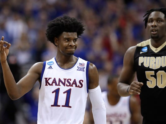Kansas guard Josh Jackson (11) celebrates in front of Purdue forward Caleb Swanigan (50) after making a 3-point basket during the second half of a regional semifinal of the NCAA men's college basketball tournament, Thursday, March 23, 2017, in Kansas City, Mo. (AP Photo/Charlie Riedel)