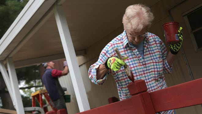 Kris Dietz of Kalamazoo, Michigan, helps paint the porch of a trailer for Blue Rose Mission on Tuesday.