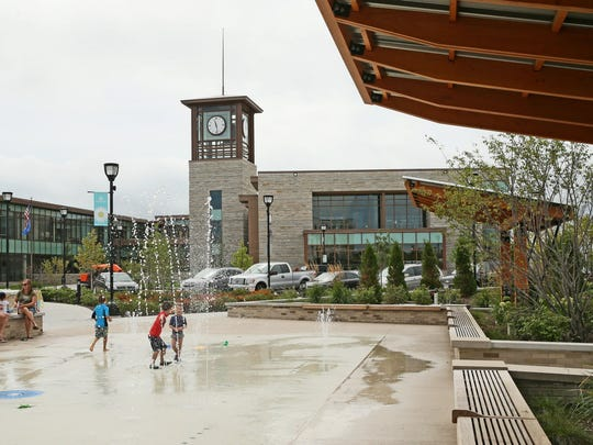 Children play on the splash pad next to the new Oak Creek City Hall and library at the Drexel Town Square development in Oak Creek.