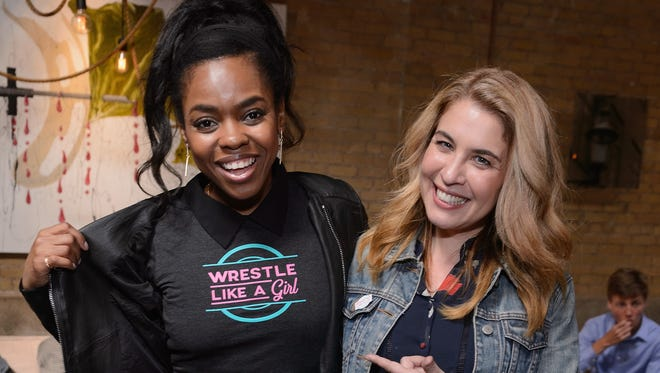 """First Match"" star Elvire Emanuelle and writer/director Olivia Newman point at Emanuelle's ""Wrestle like a girl"" shirt at a SXSW party."