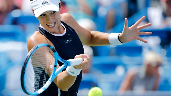 Garbiñe Muguruza returns a shot in the first set of the women's finals match between Garbiñe Muguruza and Simona Halep during the Western & Southern Open at the Lindner Family Tennis Center in Mason, Ohio, on Sunday, Aug. 20, 2017. Muguruza won the championship in straight sets, 6-1, 6-0, over the 2-seeded Halep.