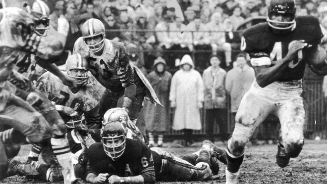 Gale Sayers (40) races out of the reach of a 49ers defender en route to one of his record six touchdowns in the mud as the Bears won 61-20 at Wrigley Field.