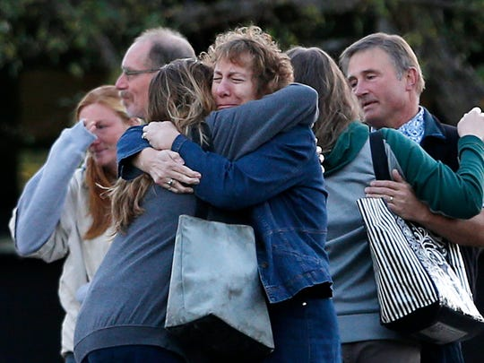 Faculty members embrace as they are allowed to return to Umpqua Community College on Oct. 5 in Roseburg, Ore. The campus reopened to faculty for the first time since Oct. 1, when armed suspect Chris Harper-Mercer killed multiple people and wounded several others before taking his own life at Snyder Hall.