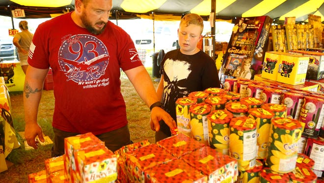 A new state law means residents won't have to sign a paper stating that they are buying fireworks for agricultural or fishery use. Aaron Nichols and his son Liam peruse offerings at the KaBOOM Fireworks tent in Butler North last July 3.