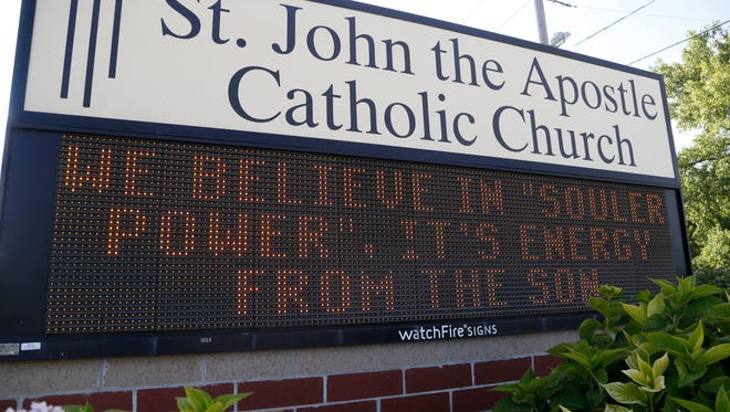 A message celebrating the church's solar power usage shows in the sign in front of the church Saturday, Aug. 12, 2017, at St. John the Apostle Catholic Church in Norwalk.