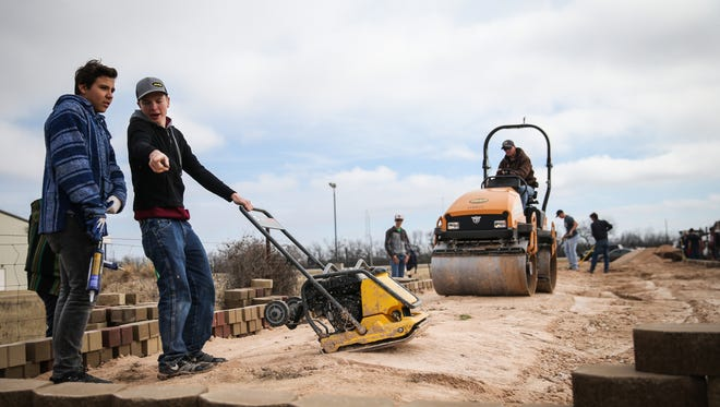 Kevin Franke talks to a volunteer while helping with construction of a raised viewing area for the sensory trail Saturday, Jan. 6, 2018, at Sonrisas Trails.