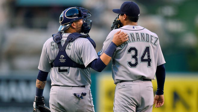 Seattle Mariners catcher Jesus Sucre, left, talks with starting pitcher Felix Hernandez during the first inning of a baseball game against the Los Angeles Angels, Saturday, Sept. 26, 2015, in Anaheim, Calif.