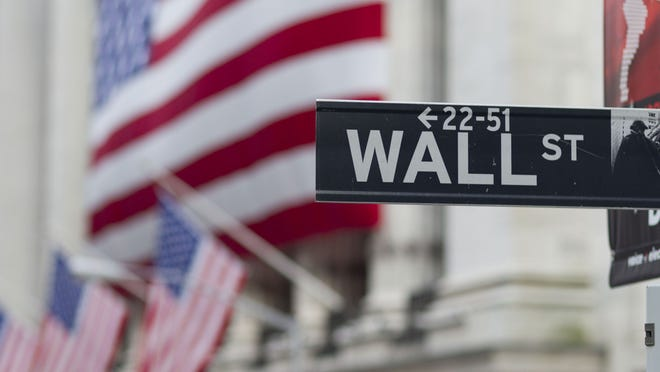 In this Aug. 8, 2011, file photo, a Wall Street sign hangs near the New York Stock Exchange.
