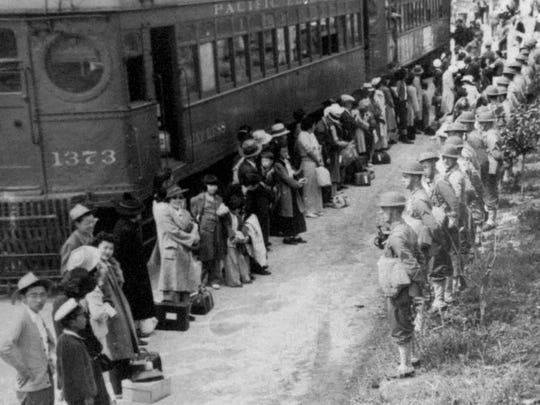 People of Japanese descent line up for a train that