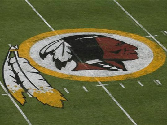 FILE - In this Aug. 7, 2014 file photo, the Washington Redskins logo is seen on the field before an NFL football preseason game against the New England Patriots in Landover, Md.