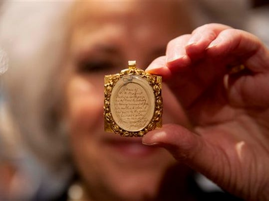 Gallery assistant Sandra Handley poses for photographs with a lock of Wolfgang Amadeus Mozart's hair, contained in a 19th-century gilt locket at the Sotheby's auction house in London, Tuesday, May 26, 2015.