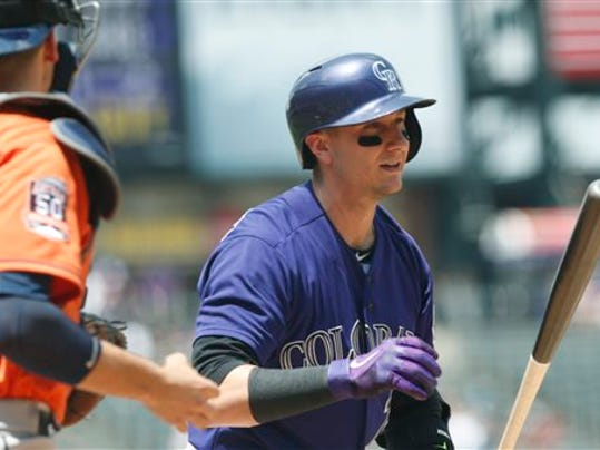 Colorado Rockies' Troy Tulowitzki, right, reacts after striking out as Houston Astros catcher Jason Castro looks on in the first inning of an interleague baseball game Thursday, June 18, 2015, in Denver.