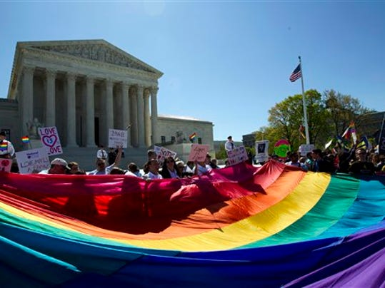 Demonstrators stand in front of a rainbow flag in front of Supreme Court in Washington on April 28, 2015.
