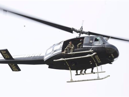 A police helicopter patrols a swampy area near route 59 and Rollins in Fox Lake, Ill.,  where a manhunt is in progress after an officer was shot on Tuesday, Sept. 1, 2015.