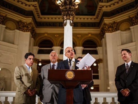 Senate Democrat Vince Hughes, D-Philadelphia, waves the Republican version of the budget during a news conference after Republicans it was sent to the governor for his signature at the state Capitol, Tuesday, June 30, 2015, in Harrisburg, Pa. Pennsylvania Democratic Gov. Tom Wolf vetoed the Republican-crafted spending plan that the GOP's huge majorities in the state Legislature sent to him just hours before the state government's fiscal year ended.