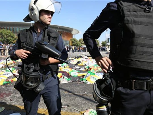 Turkish police officers secure the area at the site of an explosion, where the bodies of victims were covered with flags and banners,  in Ankara, Turkey, Saturday, Oct. 10, 2015. The two bomb explosions targeting a peace rally in the capital Ankara has killed dozens of people and injured scores of others. The explosions occurred minutes apart near Ankara's main train station as people were gathering for the rally, organized by the country's public sector workers' trade union and other civic society groups. The rally aimed to call for an end to the renewed violence between Kurdish rebels and Turkish security forces.