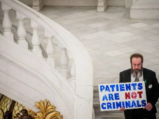 A demonstrator holds a sign in support of medical marijuana during a cannabis reform rally at the Capitol rotunda in Harrisburg in March 2014.