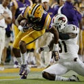 BATON ROUGE, LA - SEPTEMBER 13:  Travin Dural #83 of the LSU Tigers is brought down by Lenzy Pipkins #31 of the Louisiana Monroe Warhawks during the third quarter of a game at Tiger Stadium on September 13, 2014 in Baton Rouge, Louisiana.  LSU won the game 31-0.  (Photo by Stacy Revere/Getty Images)