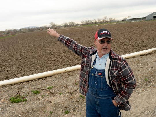 "In this April 2, 2018, photo, Alan Bangerter stands in front of 20-acre field where he grows vegetables in Farmington, Utah. Bangerter contends there are other plots of land where soccer fields could be placed without harming ""a productive farm."""