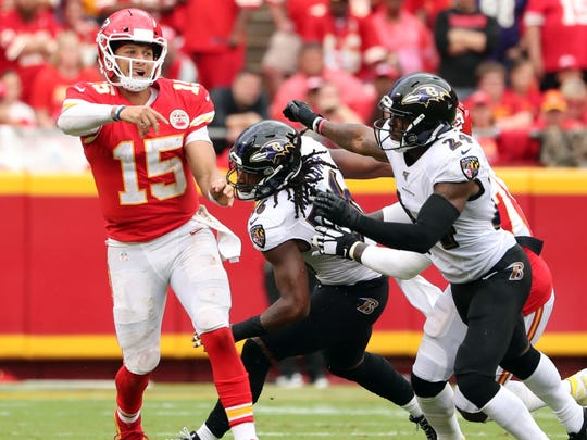 Sep 22, 2019; Kansas City, MO, USA; Kansas City Chiefs quarterback Patrick Mahomes (15) throws a pass as Baltimore Ravens linebacker Tim Williams (56) and cornerback Brandon CarrÊ(24) defend during the second half at Arrowhead Stadium. Mandatory Credit: Jay Biggerstaff-USA TODAY Sports