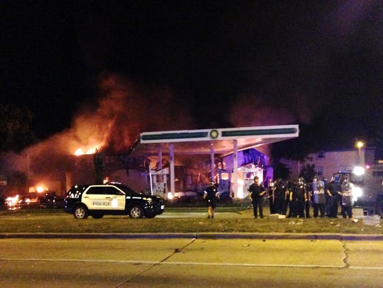 A burning gas station as dozens of people protest following