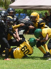 Saints player Damian J. Cruz (3) is taken down by the Eagles defense during their Triple J Ford GNYFF Youth Football League game at Eagle Field in Mangilao on Aug. 30.
