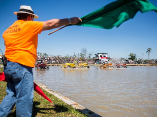 The race flagger signals the start of the race during the Swamp Buggy Races Spring Classic at the Florida Sports Park on Saturday, March 3, 2018.