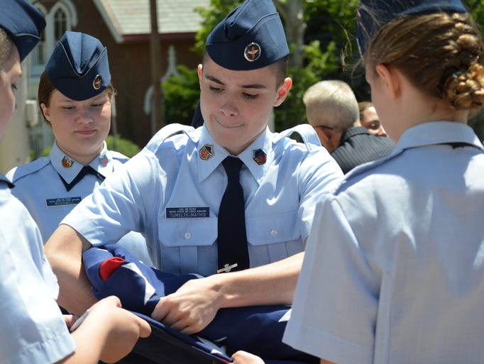 With assistance from fellow cadets in the Civil Air Patrol Cumberland Composite Squadron, cadet Nicholas Tumelty-Mathis of Vineland makes the final fold of a huge American flag that was suspended by a city fire during Saturday's Flag Day ceremony.