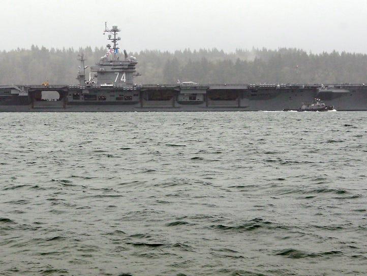 The USS John C. Stennis sails through the heavy rain