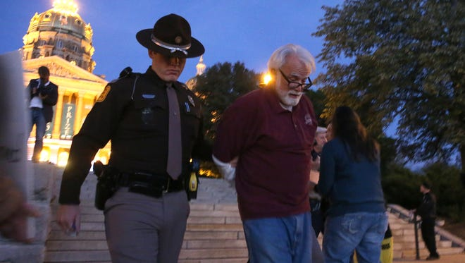 An Iowa State Patrolman arrests Frank Cordaro of Des Moines during an Occupy World Food Prize rally at the State Capitol grounds on Thursday, Oct. 16, 2014, in Des Moines, Iowa.