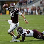 Texas A&M quarterback Kyle Allen avoids the tackle attempt by Mississippi State linebacker Beniquez Brown during the first half Saturday in College Station, Texas.