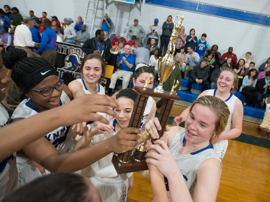 Catholic's Michaelyn Foster (12), right, holds the Area Championship trophy with the rest of her team after the AHSAA Area Championship basketball game on Friday, Feb. 10, 2017, in Montgomery, Ala. Catholic defeated BTW 38-37.