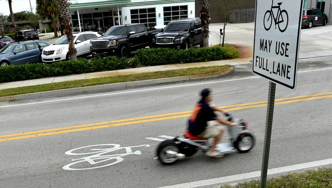 A motorcyclist passes by a sharrow, a shared–lane marking on the road, traveling south along Old Dixie Highway between State Road 60 and 16th Street, Tuesday, Jan. 9, 2018, in Vero Beach. The sharrow markings and signage inform bicyclists and motorists that the roadway in the designated area is to be shared among them.