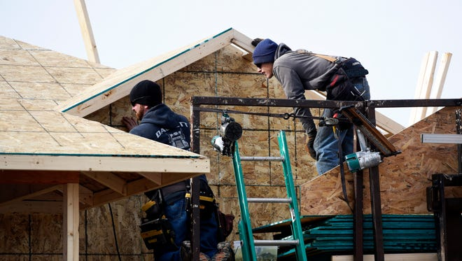 Construction workers for Paul Fick Homes finish the roof of a house in southern Sioux Falls. In Sioux Falls, there were more single family homes built last year than any year since the recession.