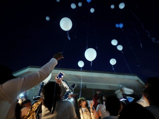 Friends and family release balloons during a candlelight