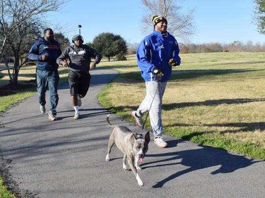 Jonathan Roque (front) with his dog Roxi and Brandon Wilkinson (back, right) and Dennis Sapp (far left) run laps around the track at Compton Park Saturday. The Redefine Project, a community service organization, was hosting a community service event.