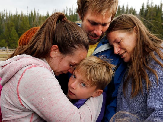 Malachi Bradley, center, is reunited with his family, in Uintah County, Utah, after being lost near a remote mountain lake near the Wyoming border on Sunday.
