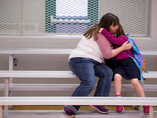 Savannah Loehr, 6, gets a hug from mom, Christa Loehr, before heading to her Dexter Elementary School classroom Wednesday morning. The two, as well as sisters Allie, 11, and Isabel, 8, had walked with nearly 110 students, teachers and parents to school from Lorraine Park as part of National Walk to School Day.