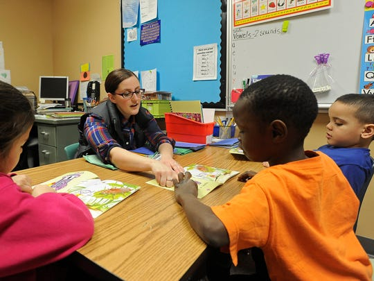 Kelsey Ellens, LIA Teacher, reads with Estrella Castaneda, Gamr Dokman and Tariku Tamire at Terry Redlin Elementary in Sioux Falls, S.D., Monday, Feb. 22, 2016.