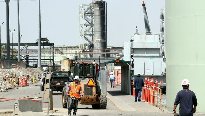 Workers are seen guiding vehicles on the power plants main road, Tuesday, Aug. 25, 2015, during a tour of the Four Corners Power Plant in Fruitland.